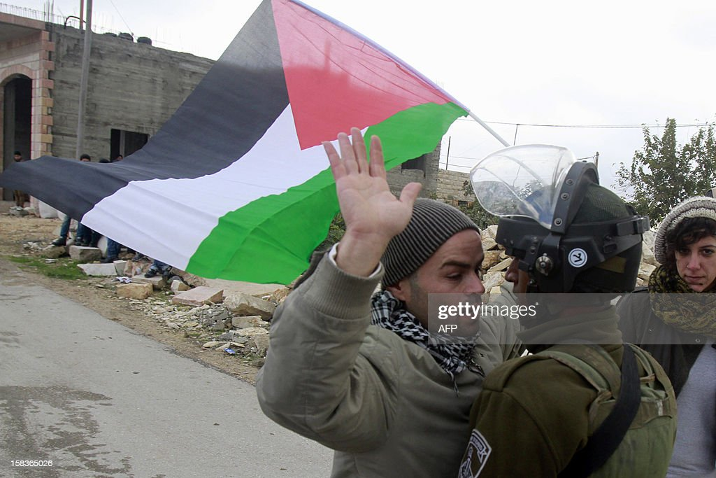 A Palestinian man confronts an Israeli soldier during a weekly protest against Israel's controversial separation barrier in the West Bank village of Maasarah near Bethlehem on December 14, 2012.AFP PHOTO/MUSA AL SHAER