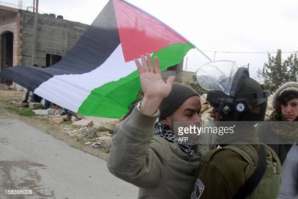 A Palestinian man confronts an Israeli soldier during a weekly protest against Israel's controversial separation barrier in the West Bank village of...