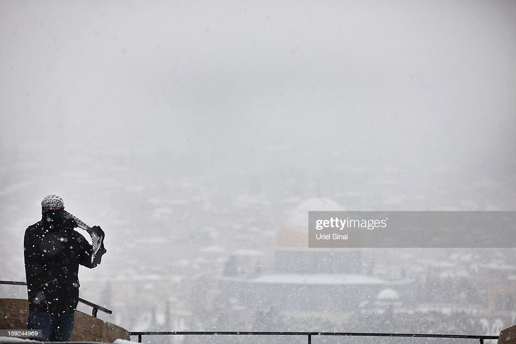 A Palestinian man covers his face as snow covers the Dome of the Rock at the Al-Aqsa mosque compound behind him on January 10, 2013 in the old city in east Jerusalem, Israel.