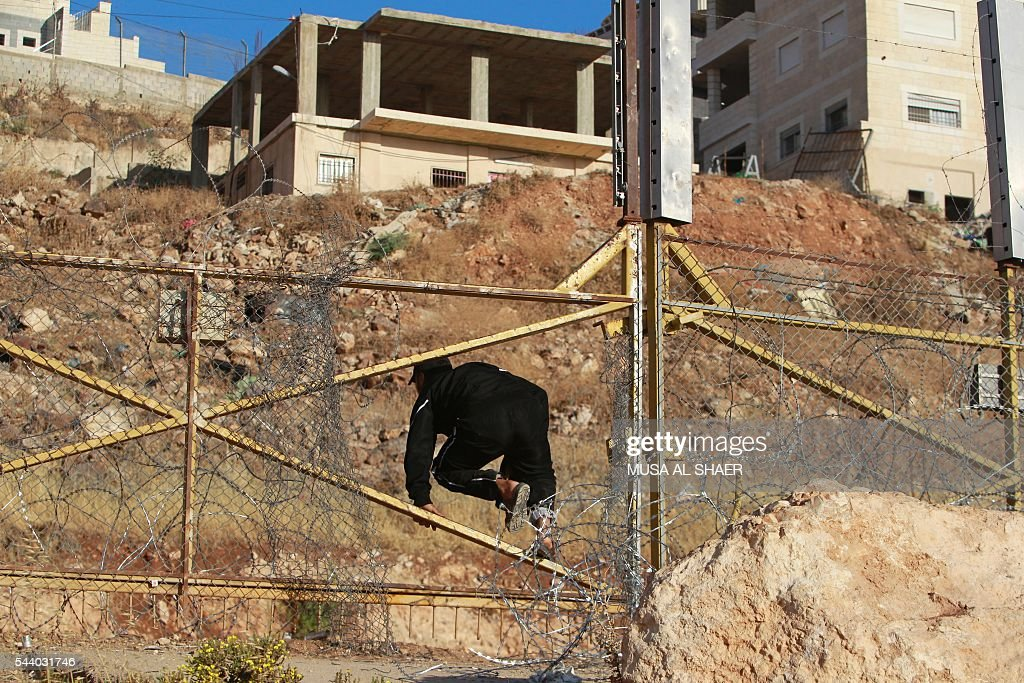 A Palestinian man crosses through a gap in the barbed-wire gate part of the controversial Israeli separation fence between the West Bank town of Bethlehem and Jerusalem, in an attempt to reach the Al-Aqsa Mosque compound in Jerusalem, after Israeli police prevented Palestinians from crossing to pray on the fourth and last Friday of the Muslim holy month of Ramadan, on July 1, 2016. Israeli authorities announced on June 28 they were closing Jerusalem's flashpoint Al-Aqsa mosque compound to non-Muslim visitors until the end of the Muslim holy month of Ramadan after a series of clashes between worshippers and Israeli police. Clashes have been taking place every morning since the beginning of the week over Jewish visits to the site, with youths throwing stones and security forces firing tear gas and sponge-tipped bullets. / AFP / MUSA
