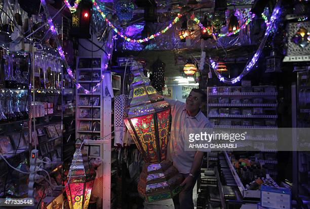 A Palestinian man decorates his shop at the entrance of the AlAqsa mosque compound in the old city of Jerusalem on June 16 as Muslims around the...