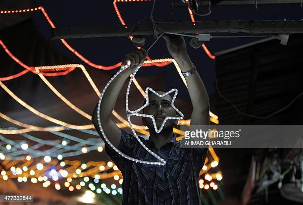 A Palestinian man decorates his shop with fairy lights near the entrance of the AlAqsa mosque compound in the old city of Jerusalem on June 16 as...
