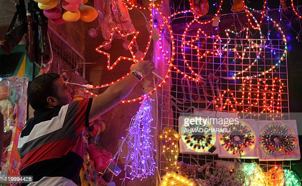 A Palestinian man decorates his shop with festive lights in the old city of Jerusalem on July 28 2011 for the upcoming Muslim holy fasting month of...