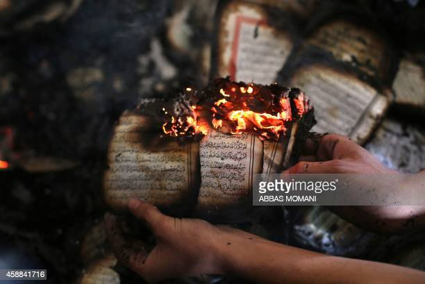A Palestinian man displays a copy of Islam's holy book the Koran still burning inside a mosque that was set ablaze by Israeli settlers in alMughayir...