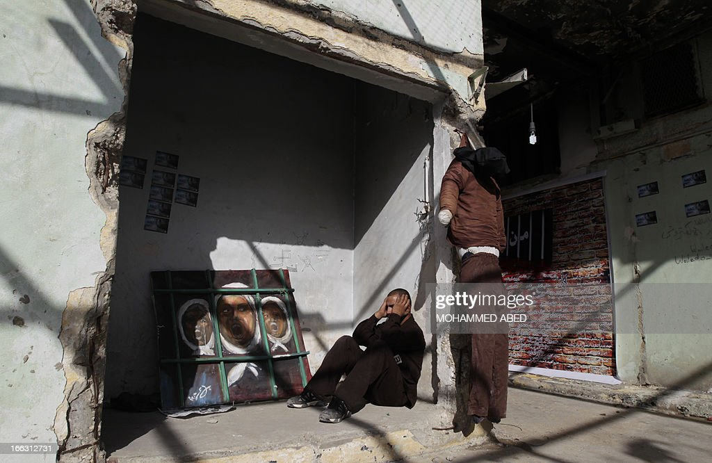 A Palestinian man dressed as a prisoner sits inside a building which used to be an Israeli prison to keep Palestinians during Israel's occupation of Gaza, on April 11, 2013, as part of a tour organized by Hamas to show the facility that has now turned into a memorial center, in Gaza City. Israel has evacuated its settlements and army posts in the Gaza Strip in 2005 . AFP PHOTO/MOHAMMED ABED