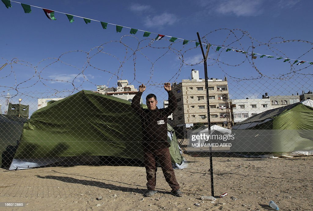 A Palestinian man dressed as a prisoner stands inside a building which used to be an Israeli prison to keep Palestinians during Israel's occupation of Gaza, on April 11, 2013, as part of a tour organized by Hamas to show the facility that has now turned into a memorial center, in Gaza City. Israel has evacuated its settlements and army posts in the Gaza Strip in 2005 .