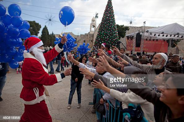 Palestinian man dressed in a Santa Claus costume gives out balloons outside the Church of the Nativity on December 24 2014 in Bethlehem West Bank...