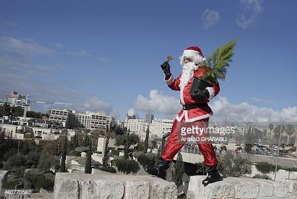 A Palestinian man dressed up as Santa Claus distributes Christmas trees along the wall of Jerusalem's Old City on December 22 as Christians around...