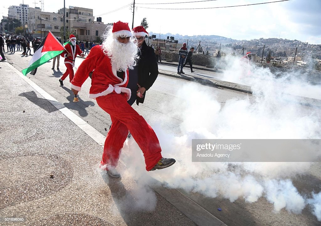 Palestinian man dressed up as Santa Claus kicks a tear gas canister during the clashes between Israeli security forces and demonstrators following a...