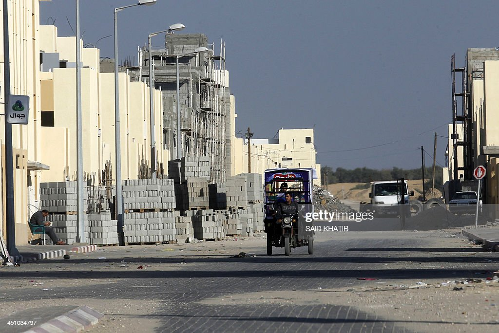 A Palestinian man drives a tricycle past building materials on the street outside new houses which are part of a project funded by the United Nations Relief and Works Agency for Palestine Refugees (UNRWA) in the southern Gaza Strip town of Rafah on November 21, 2013. The UNRWA, which is facing a 36-million dollar deficit, halted 19 out of 20 construction projects in the Hamas-controlled Gaza territory after Israel suspended the entry of all construction materials into Gaza following the discovery of a tunnel by Israeli authorities from the besieged strip into Israel in October.