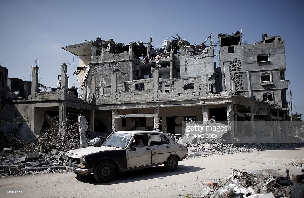 A Palestinian man drives his old Peugeot 504 car past destroyed buildings in the northern Gaza Strip city of Beit Hanun on August 22, 2014. The Hamas armed wing declared the truce efforts over after Israel carried out an abortive assassination attempt the previous day on its leader Mohammed Deif, killing his wife and two of his children.