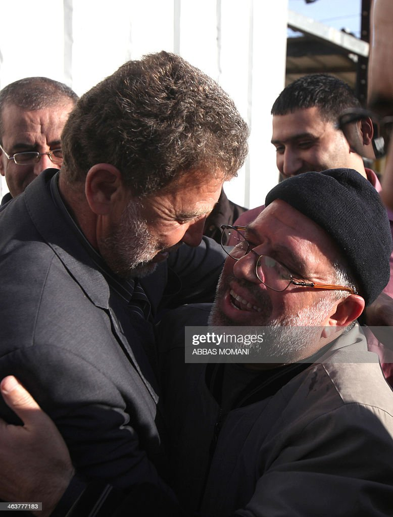 A Palestinian man embraces Sheikh Hassan Yousef (R), a prominent leader of the Hamas Islamic movement, following his release on January 19, 2014 after spending 28 months in Israel's Ofer prison, near the West Bank city of Ramallah. Yousef, who is also a member of the Ramallah-based Palestinian Legislative Council, told reporters after being released that he would work with Hamas rivals 'Fatah and other Palestinian factions to achieve reconciliation.' AFP PHOTO / ABBAS MOMANI