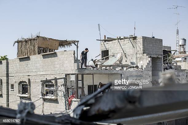 A Palestinian man from Gaza Strip's central Bureij refugee gestures while inspecting the damages on the roof of his house during the first hours of a...
