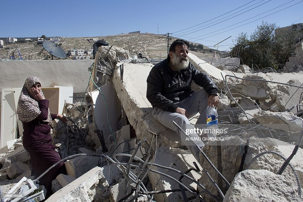 A Palestinian man from the Beshr family sits on the debris of his house after it was demolished by Israeli authorities who said it was built without municipal permission on February 5, 2014 in the Arab east Jerusalem neighborhood of Jabel Mukaber. Israel pushed forward with plans for more than 550 new homes in three settlement neighbourhoods of annexed east Jerusalem, the city council said.