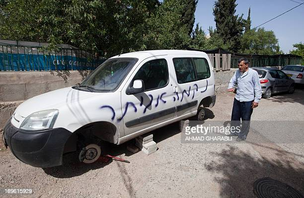 A Palestinian man gestures near his car after it was paint sprayed with the words 'price tag' reading in Hebrew in the East Jerusalem neighborhood of...