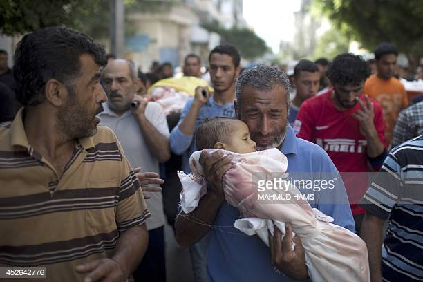 A Palestinian man grieves as he carries the body of oneyearold baby Noha Mesleh who died of wounds sustained after a UN school in Beit Hanun was hit...