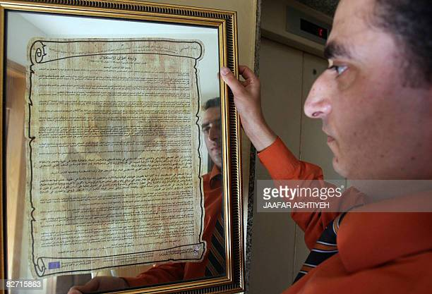 A Palestinian man hangs on the wall a copy of the Palestinian National Charter of the Declaration of Independence written by late Palestinian poet...