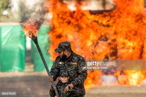 Palestinian man helps a boy set fire to an Israeli flag during a graduation ceremony for Hamas security forces in Gaza City on January 22 2017 / AFP...