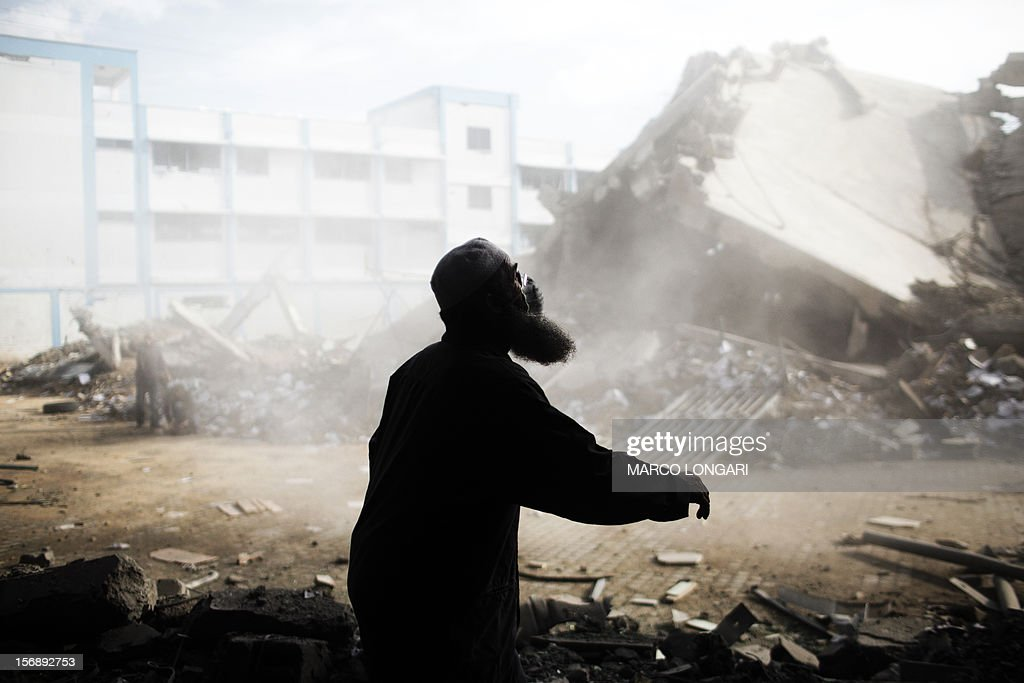 A Palestinian man helps clean the debris from the building of the Ministry of Interior in Gaza City on November 24, 2012, after it was destroyed during an Israeli air strike on November 16, at the height of the week-long conflict between Israel and Gaza militants. Iran's President Mahmud Ahmadinejad congratulated Gaza's Hamas prime minister Ismail Haniya in a telephone call on a 'great victory' over Israel, the two sides said.