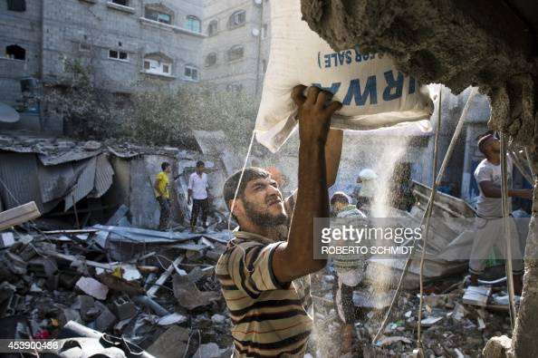 A Palestinian man helps remove a bag of flour from a house that was destroyed by an Israeli airstrike in Gaza City on August 21 2014 The owners of...