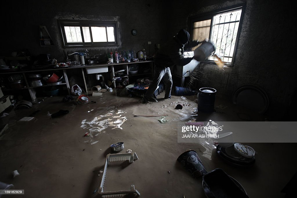 A Palestinian man helps to remove water from a flooded house in the West Bank city of Tulkarem on January 9, 2013. Israel and the Palestinian territories have been lashed by heavy rain and high winds since January 6, which has caused flooding across the region.
