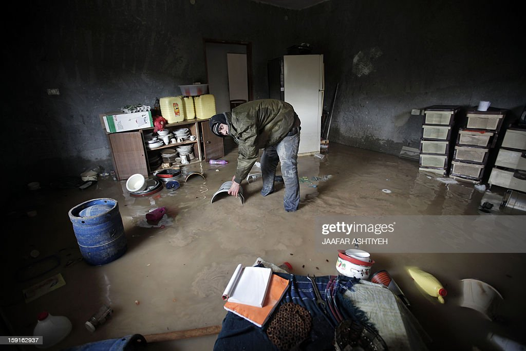 A Palestinian man helps to remove water from a flooded house in the West Bank city of Tulkarem on January 9, 2013. Israel and the Palestinian territories have been lashed by heavy rain and high winds since January 6, which has caused flooding across the region. AFP PHOTO/JAAFAR ASHTIYEH