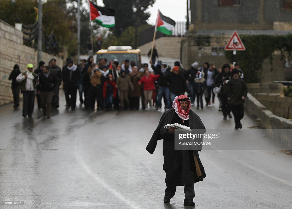 A Palestinian man holding a pack of eggs takes part in a march organized by inhabitants of the West Bank village Nabi Saleh on December 21, 2012, to protest against the expansion of Jewish settlements on Palestinian land. AFP PHOTO/ABBAS MOMANI