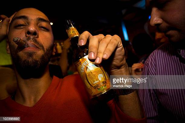 Palestinian man holds a bottle of Palestinianmade Taybeh beer in the Orjuwan Lounge on June 24 2010 in Ramallah West Bank Nightlife in Ramallah is on...