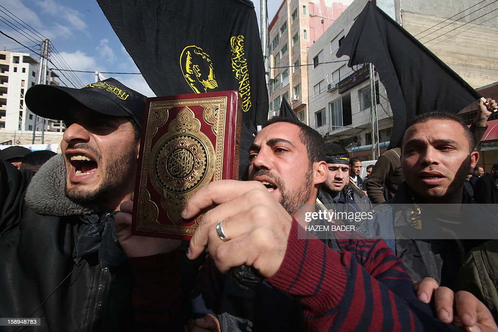 A Palestinian man holds a Koran as he chants slogans with other demonstrators waving Islamic Jihad movement flags during a demonstration in support with Palestinian prisoners on hunger strike against administrative detention in the West Bank city of Hebron on January 4, 2013. AFP PHOTO/HAZEM BADER