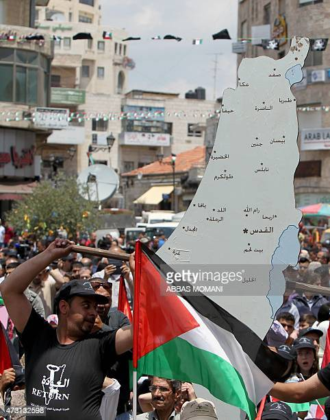 A Palestinian man holds a large map during a demonstration on May 13 2015 in the West Bank city of Ramallah to commemorate the 'Nakba' or...