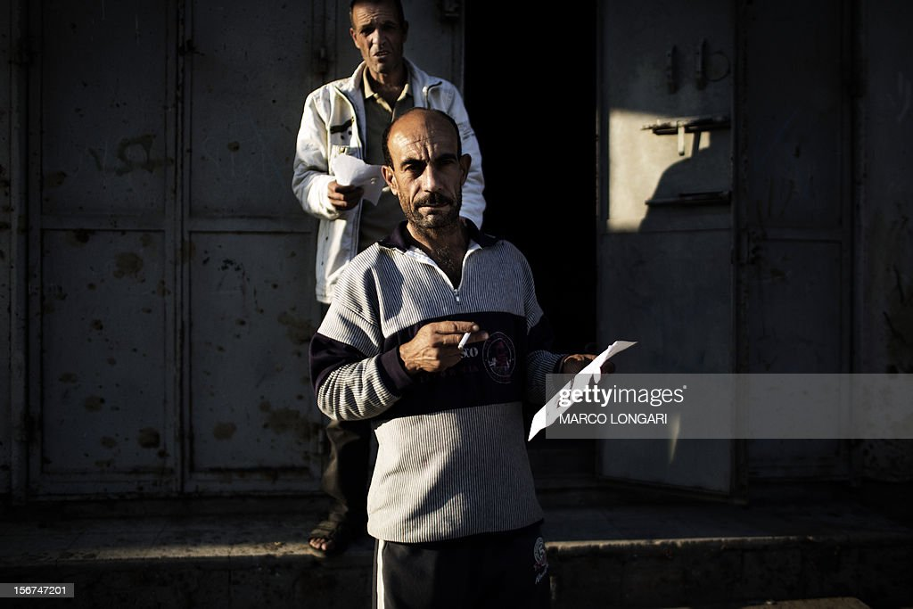 A Palestinian man holds a leaflet dropped by Israeli air force in the Tufah neighbourhood of Gaza City on November 20, 2012, urging residents of certain districts of the city to evacuate their homes 'immediately' amid fears the military was poised to launch a ground operation.