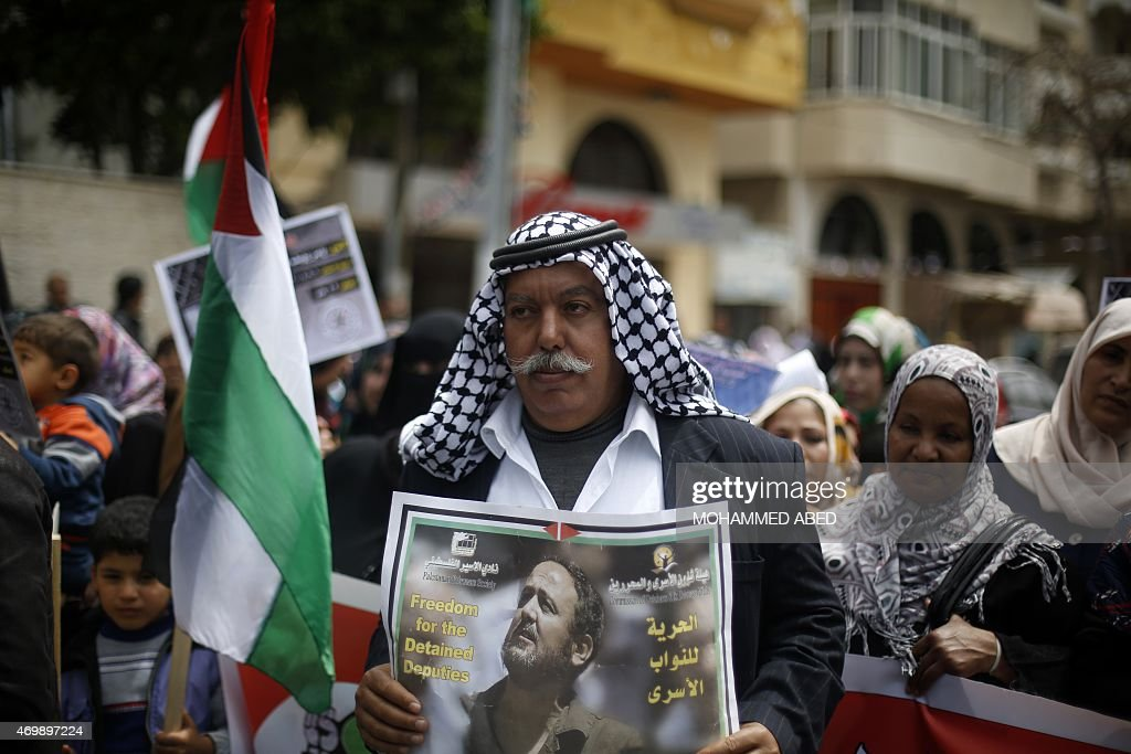 A Palestinian man holds a portrait of Fatah leader Marwan Barghuti, who is imprisoned in an Israeli jail, during a protest marking Palestinian Prisoners' Day in Gaza City on April 16, 2015 .