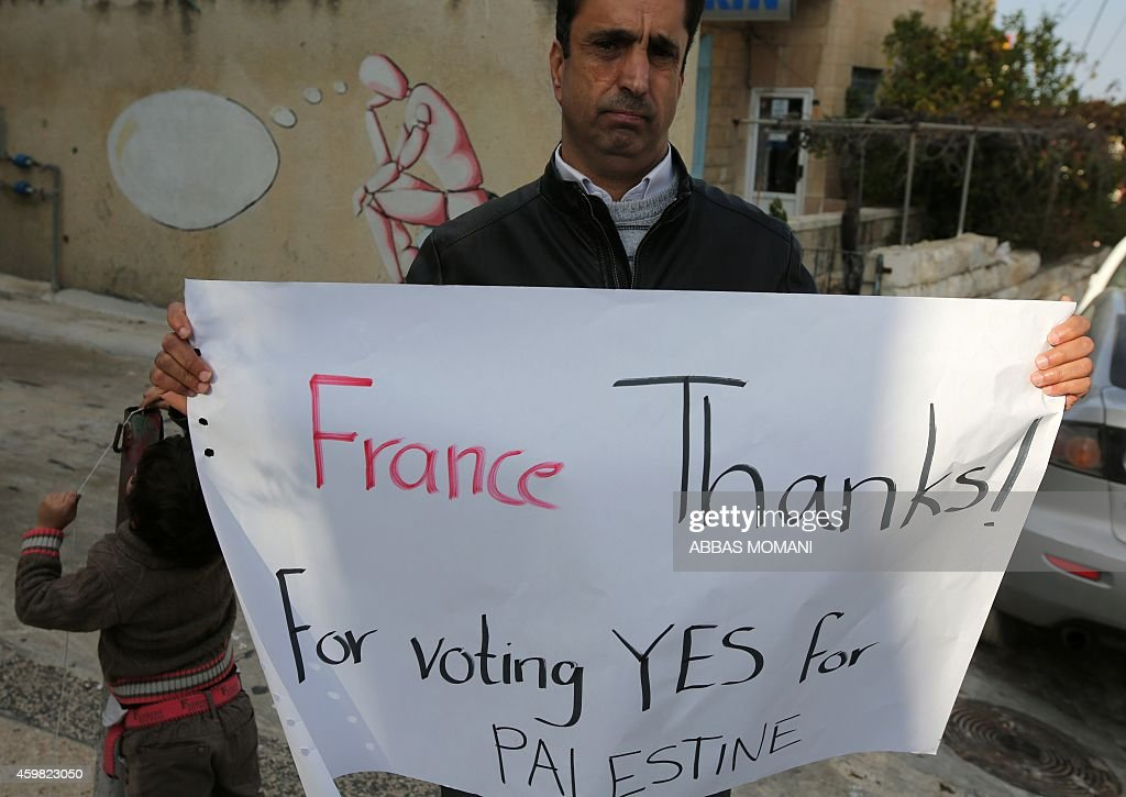 A Palestinian man holds a poster as he calls for France to vote for the recognition of a Palestinian State outside a French and German language...