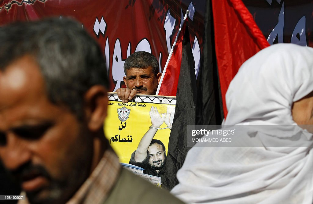 A Palestinian man holds a poster of jailed Fatah leader Marwan Barghuti as he takes part in a demonstration calling for the release of Palestinian prisoners held in Israeli jails outside the Red Cross office in Gaza City on December 17, 2012.