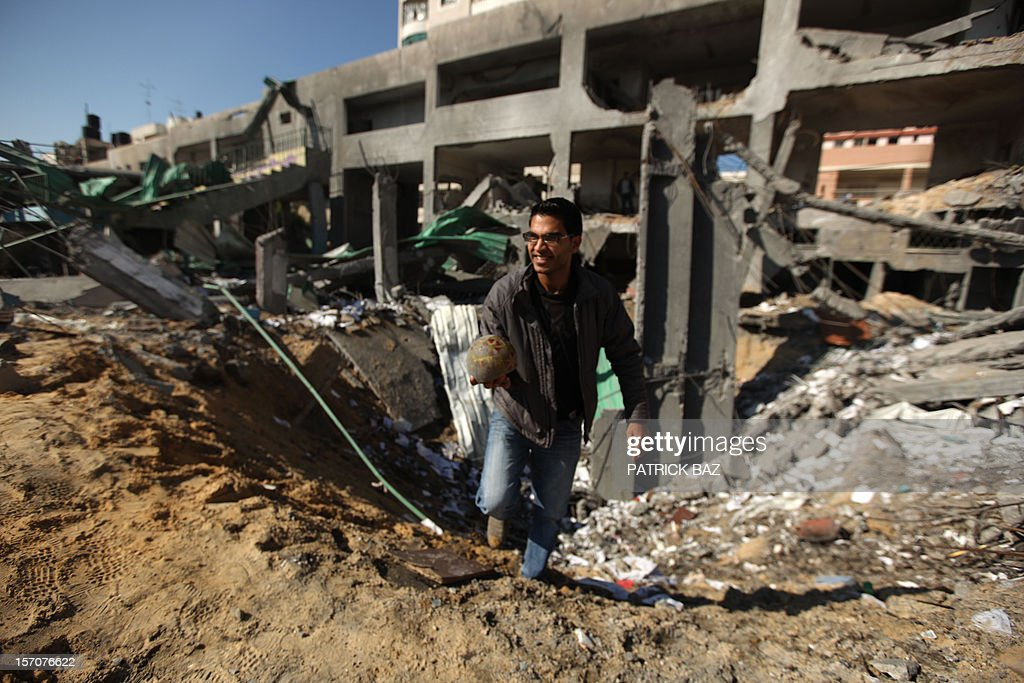 A Palestinian man holds a soccer ball found in the rubble of the bombed Palestine football stadium in Gaza City on November 28, 2012. The stadium was bombed by the Israeli airforce during a conflict between the ruling Hamas party and the Israeli military between 14 and 21 November 2012. AFP PHOTO / PATRICK BAZ