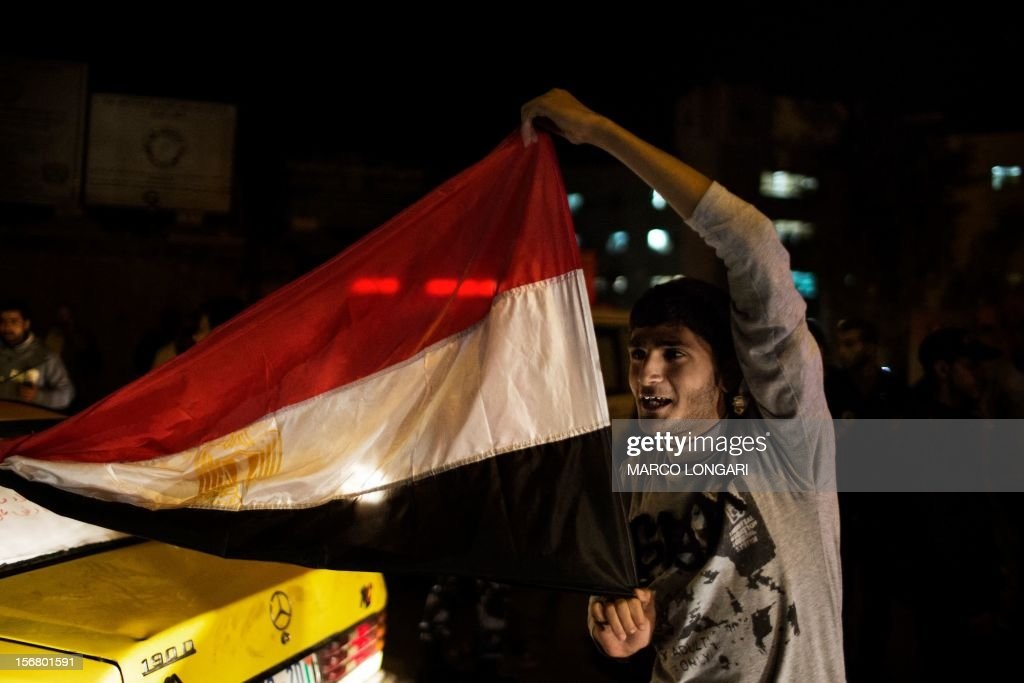 A Palestinian man holds an Egyptian flag while celebrating the beginning of the truce in Gaza City November 21, 2012. Palestinians in Gaza took to the streets to celebrate the start of a truce deal with Israel that was announced in Egypt on the eighth day of violence in and around Gaza.AFP PHOTO/MARCO LONGARI