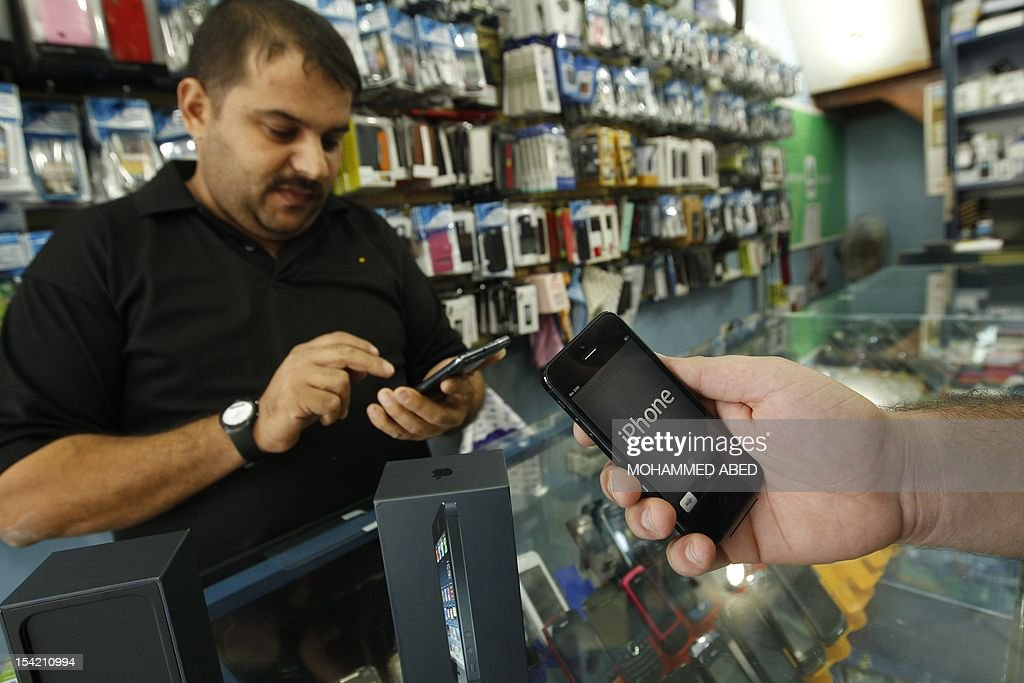 A Palestinian man holds Apple's new iPhone 5 at a mobile phone store in Gaza City on October 16, 2012. Apple's new iPhone 5 is selling well in the Gaza Strip despite inflated prices, reaching the Palestinian enclave via smuggling tunnels even before high-tech hub Israel next door.