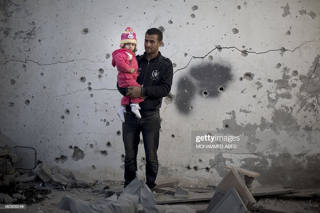 A Palestinian man holds his daughter next to a damaged building following overnight Israeli air strikes in Gaza City on January 16, 2014. Israeli air strikes in the Gaza Strip against training camps used by the armed wing of the territory's Hamas rulers left four children and a woman wounded, Palestinian medical sources said.