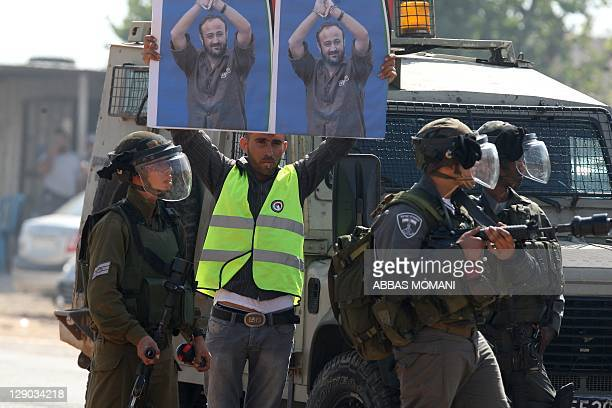 A Palestinian man holds up portraits of jailed Palestinian Fatah leader Marwan Barghuti near Israeli forces during a demonstration calling for the...
