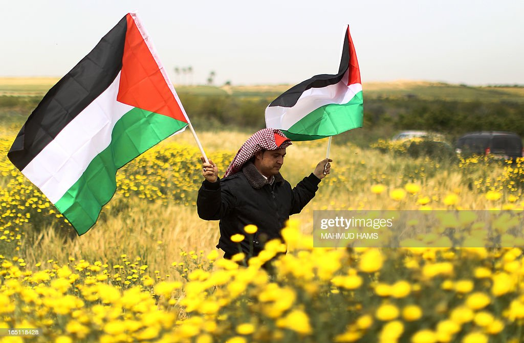 A Palestinian man holds up the national flag as he walks across a field during a rally marking Land Day in Beit Hanun in the northern Gaza Strip close to the border with Israel on March 31, 2013. The annual demonstrations mark the deaths of six Arab Israeli protesters at the hands of Israeli police and troops during mass protests in 1976 against plans to confiscate Arab land in the northern Galilee region.