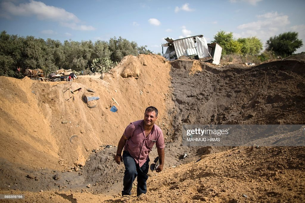 A Palestinian man inspects a crater on August 22 2016 in Beit Lahia in the northern Gaza Strip following an Israeli airstrike the day before that...