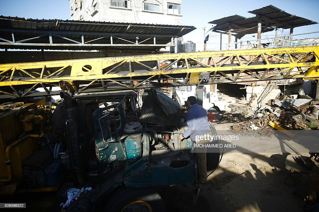 A Palestinian man inspects a damaged vehicle at his workshop after it was hit by an Israeli air strike in Gaza City, in the early hours of May 5, 2016. Israeli air strikes hit four Hamas sites in Gaza overnight, the military said, following earlier raids as tensions flared along the border of the Palestinian territory. The spike in cross border violence has raised concerns for a ceasefire that has held since the last round of hostilities in Gaza ended in summer 2014. / AFP / MOHAMMED