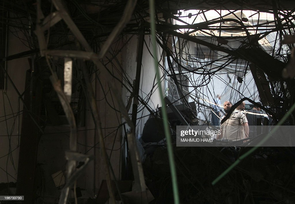 A Palestinian man inspects a destroyed branch of the Islamic National Bank following an Israeli air strike in Gaza City, on November 20, 2012. Seven Palestinians were wounded in strikes on Gaza overnight, but no one was killed in the first night without fatalities since the Israeli air campaign began nearly a week ago. AFP PHOTO/MAHMUD HAMS