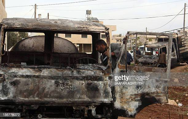 A Palestinian man inspects his burnt truck that is believed to have been torched in a 'price tag' attack which are usually carried out by extreme...