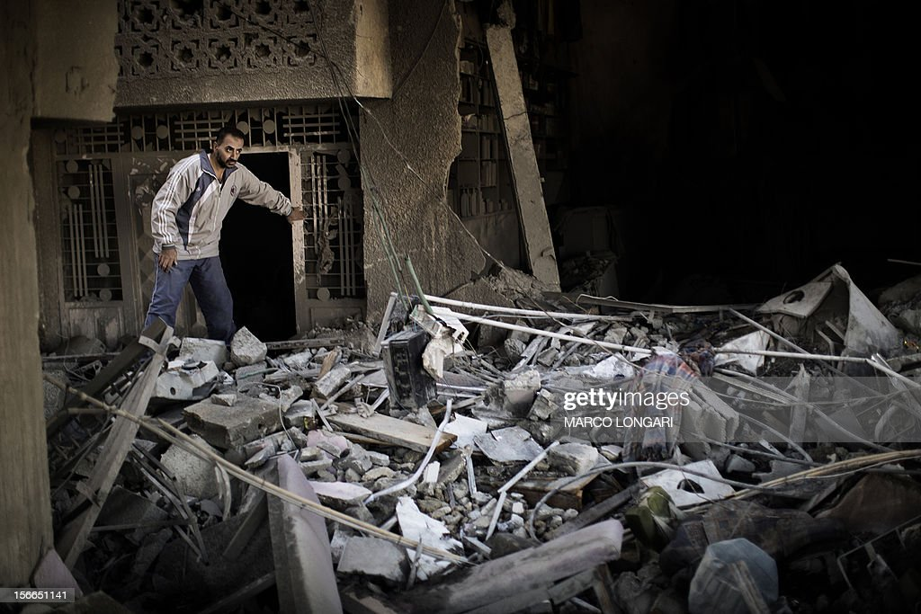 A Palestinian man inspects his damaged house following Israeli air strikes the village of Beit Lahia in the northern Gaza Strip on November 18, 2012. Israeli war planes hit a Gaza City media centre and homes in northern Gaza in the early morning, as the death toll mounted, despite suggestions from Egypt's President Mohamed Morsi that there could be a 'ceasefire soon.'AFP PHOTO/MARCO LONGARI