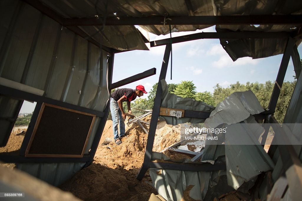 A Palestinian man inspects the rubble of a makeshift dwelling on August 22 2016 in Beit Lahia in the northern Gaza Strip following an Israeli...