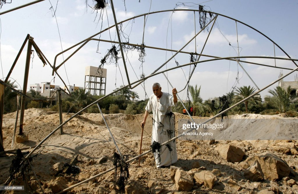 A Palestinian man inspects the site of an Israeli strike, ahead of the announcement of a five-day temporary ceasefire in Khan Younis town of Gaza, on August 14, 2014. A new five-day ceasefire between Palestinian factions and Israel went into effect on Thursday as part of efforts aimed at reaching a permanent truce deal. The Palestinian death toll from Israel's weeks-long military onslaught on the Gaza Strip has risen to 1959, according to a Palestinian Health Ministry spokesman.