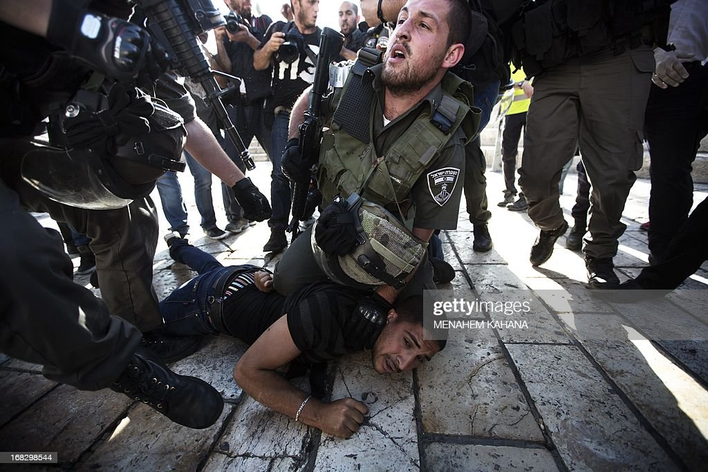 A Palestinian man is arrested by Israeli border policemen following a protest against Israelis celebrating Jerusalem Day on May 8, 2013 at the Damascus gate in Jerusalem's Old City. Jerusalem Day marks the anniversary of the 'reunification' of the city after Israel captured the Arab eastern sector from Jordan.Police, who were deployed in their thousands, arrested 13 people including two 'Arab youths' suspected of throwing water at Jews participating in the flag dance near Damascus Gate, police spokeswoman Luba Samri said in a statement. KAHANA