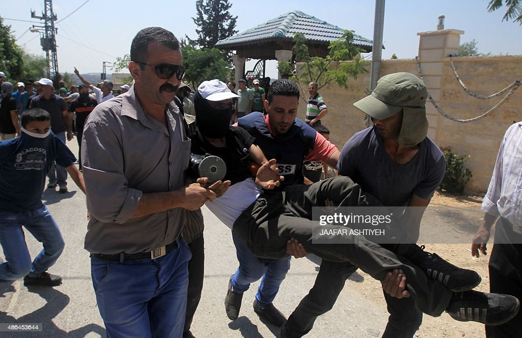A Palestinian man is carried away by fellow protesters after he was injured during clashes with Israeli security forces following a demonstration...