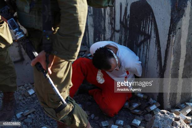 Palestinian man is detained by Israeli soldiers during the clashes between Palestinians and Israeli security forces following a protest against the...